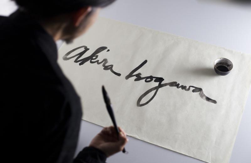 Akira Isogawa  fashion designer  using brush and paper to create calligraphy for exhibition signage  photo by Marinco Kojdanovski
